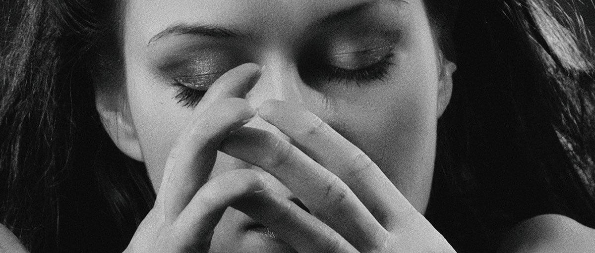 sad woman with fingers in front of her face